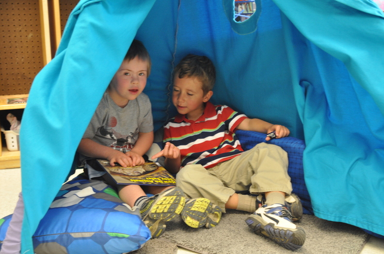 two boys reading books in a play tent